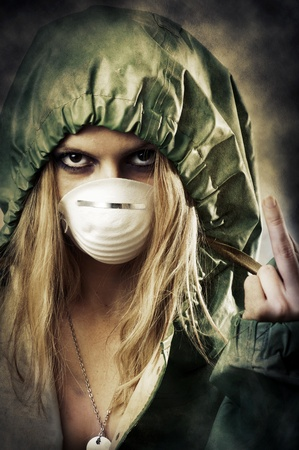 Portrait of post apocalypse girl which shows a gesture to the shot. Woman in protective suit and mask photo