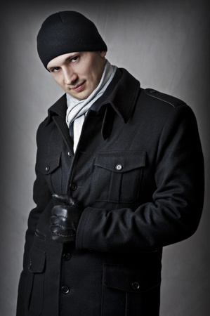 Casual. fashion portrait of sexy handsome man in black coat, hat, gloves and white scarf photo