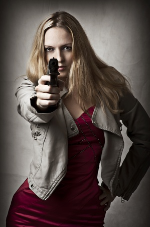 violence and trigger: Portrait of dangerous sexy blond woman with hand gun