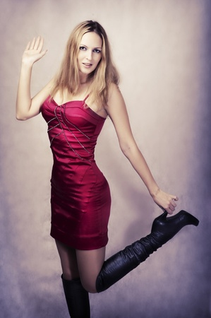 Fashion portrait of sexy happy dancing woman in high heel long black boots and fashionable red silk dress for party photo