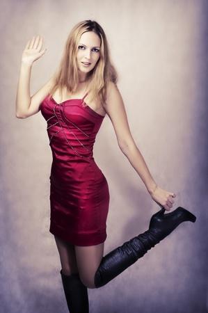 Moda retrato de mujer sexy bailando feliz en tac�n alto largas botas negras y vestido a la moda de seda roja para la fiesta Foto de archivo - 12080471