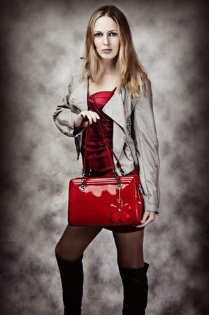 Fashion portrait of sexy woman with red fashionable patent leather bag photo
