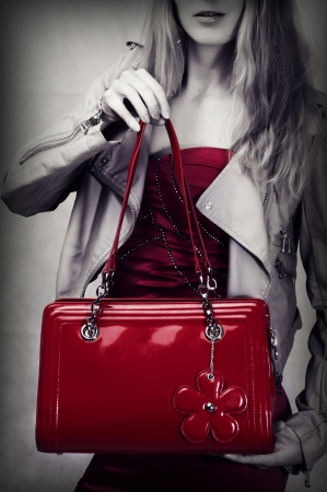 Fashion shot of red patent leather bag in woman hands photo