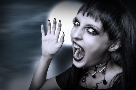 Vampire gothic style for halloween. Portrait of screaming young brunette woman with fangs photo