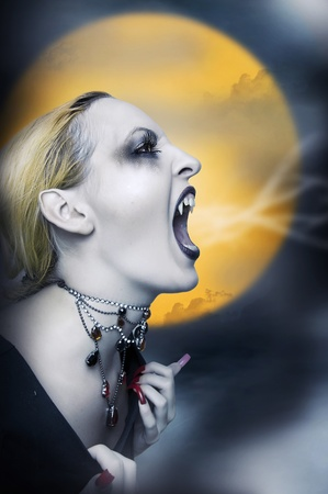 Sexy screaming vampire, witch or zombie at midnight and moonlight photo
