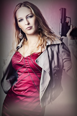 Fashion portrait of sexy dangerous woman holding gun photo