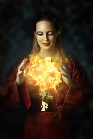 Fantasy fairytail world - portrait of yong beautiful woman - fairy, witch, elf or wizard. She making magic - casting fire ball Stock Photo - 12080476