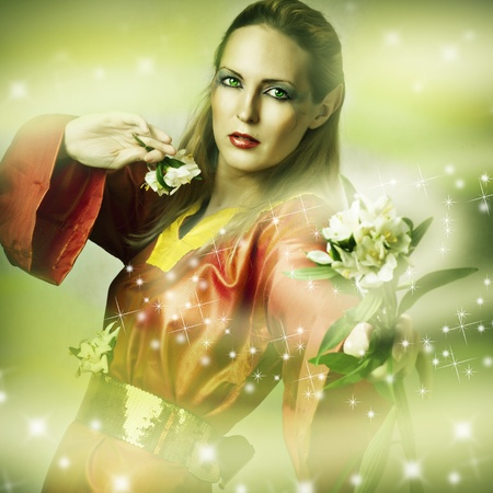 Fashion fantasy portrait of magic woman - fairytale forest elf with flower making magic Stock Photo