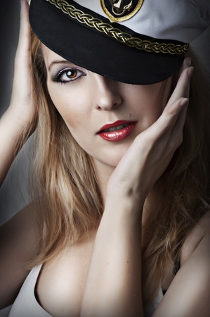 Fashion portrait of young sexy woman with red lips and captain cap photo