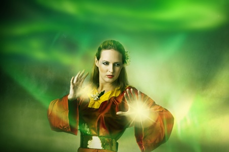 Young woman elf or witch making magic. Fantasy portrait photo