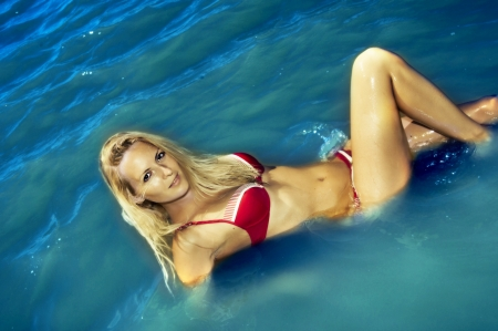 Fashion portrait of young sexy woman in red swimsuit in water. Sea or ocean resort Stock Photo - 12120698