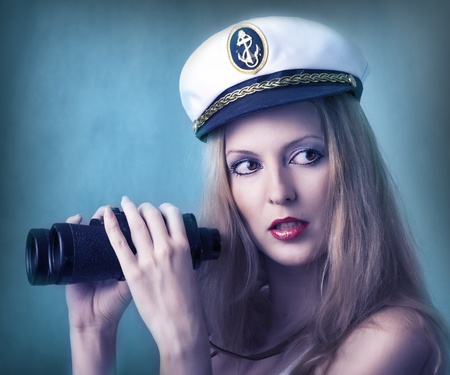 Fashion portrait of sexy woman with binocular at captain cap photo