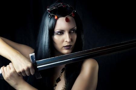 medieval swords: Guerrero Mujer joven atractiva que sostiene la espada en las manos con el pelo negro largo saludable. Foto de archivo