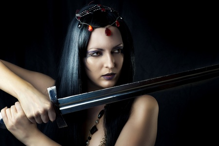 Young sexy woman warrior holding sword in hands with long healthy black hair. Stock Photo - 12120700