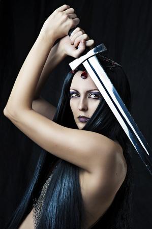 maquillaje de fantasia: Guerrero Mujer joven atractiva que sostiene la espada en las manos con el pelo negro largo saludable. Foto de archivo