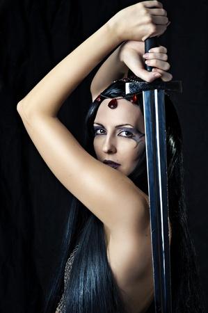 maquillaje fantasia: Guerrero Mujer joven atractiva que sostiene la espada en las manos con el pelo negro largo saludable. Foto de archivo