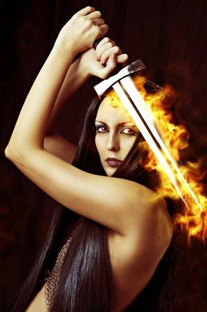 espadas medievales: Joven guerrero mujer sexy sosteniendo espada de fuego en las manos con el pelo negro largo saludable. Foto de archivo