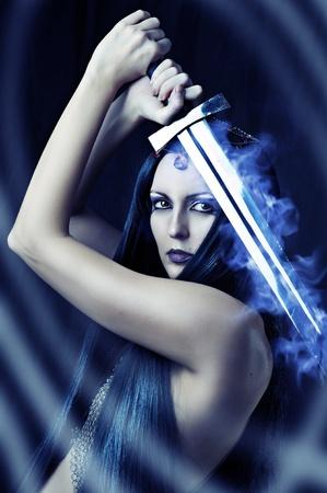 espadas medievales: Joven guerrero mujer sexy sosteniendo espada de fuego azul en las manos con el pelo negro largo saludable.