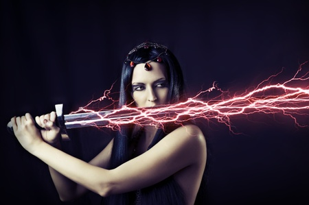 Fashion portrait of young sexy brunette woman - storm. Weather - flash lightning on her sword. mythology, fairytale or fantasy world. photo