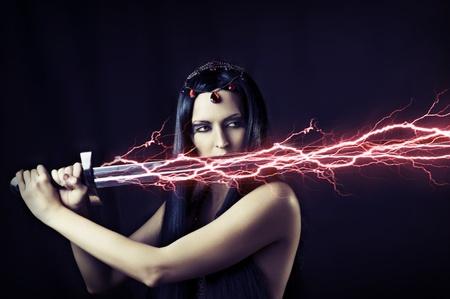 dark elf: Fashion portrait of young sexy brunette woman - storm. Weather - flash lightning on her sword. mythology, fairytale or fantasy world. Stock Photo