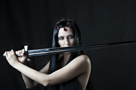 dark elf: Fashion portrait of young sexy brunette woman with sword on black background Stock Photo