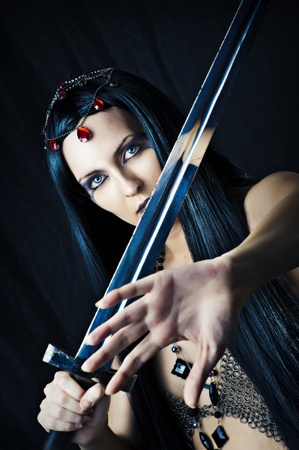 Fashion portrait of sexy brunette woman - witch. She is making magic and holding medieval sword photo