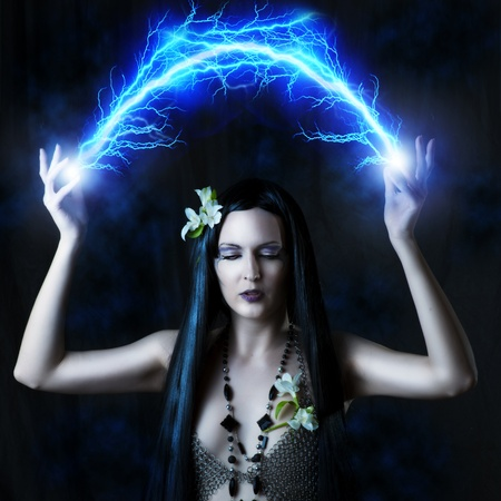 Fashion portrait of woman - witch or elf. She is making magic - arc or flash lightning