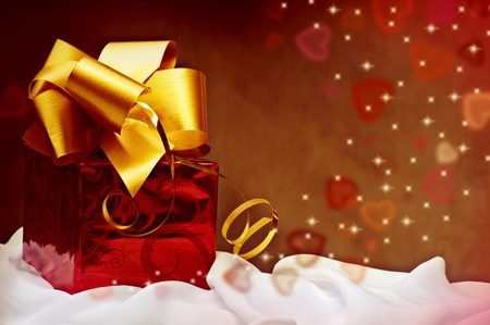 Red gift with golden ribbon with hearts. Concept card for valentines day Reklamní fotografie