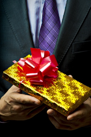 gray suit: Male hands holding gift. Present in golden box with red ribbon