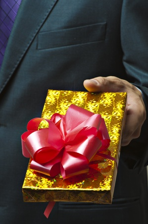Male hands holding gift. Present in golden box with red ribbon photo