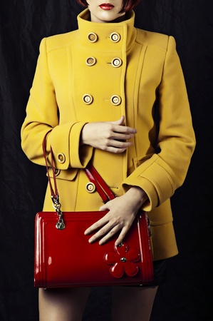 handbag: Fashion portrait of beautiful woman in yellow spring or autumn coat and with red bag
