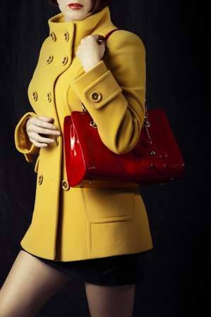 handbag model: Fashion portrait of beautiful woman in yellow spring or autumn coat with red bag