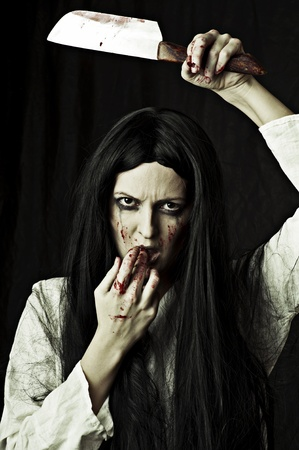 Portrait of a gory bloody and scary zombie woman on black background holding knife photo