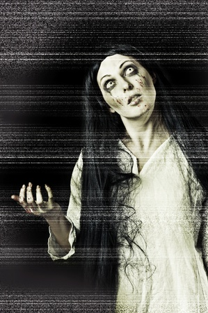 Portrait of a gory bloody and scary zombie woman on black background with television white grain (tv noise) stylization photo