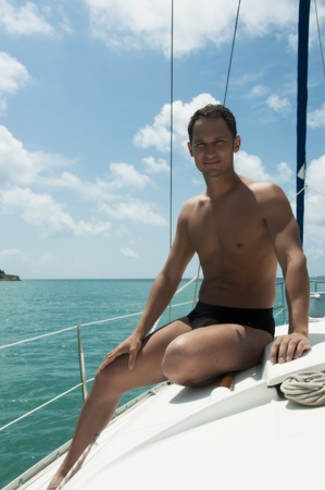 Handsome young adult man sailing on a yacht on summer day  Stock Photo - 12390507