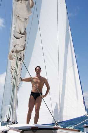 Handsome young adult man sailing on a yacht on summer day. He is about big white sail Stock Photo - 12390506