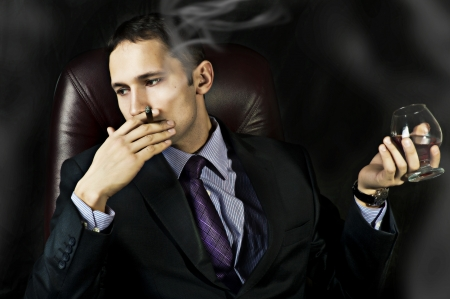 portrait of young handsome business man with Old Brandy Glass in hand and smoking cigar on black background. men's club photo