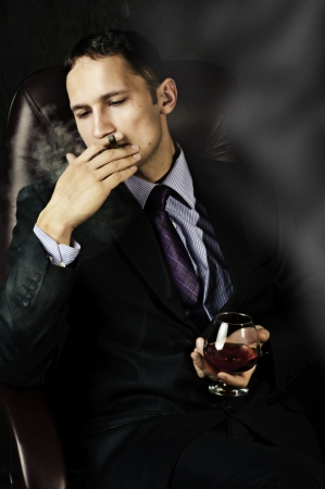 cognac:  portrait of young handsome business man with Old Brandy Glass in hand and smoking cigar on black background. mens club
