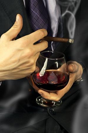cigarro: Copa de brandy viejo en la mano masculina y fumar cigarros sobre fondo negro. club de caballeros