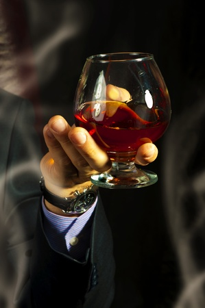 lux: Old Brandy Glass at male hand and smoking on black background. mens club Stock Photo