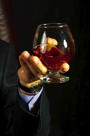 cognac: Old Brandy Glass at male hand  on black background.  Stock Photo