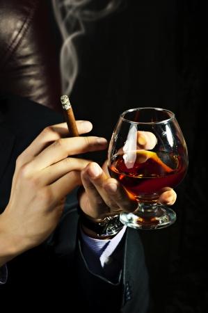 hombre fumando: Glass Brandy viejo en la mano masculina y fumando un cigarro en fondo negro.