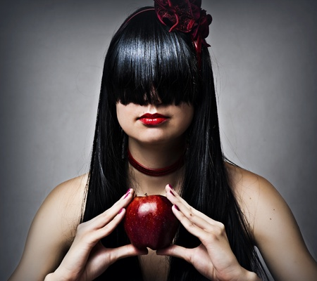 Fashion portrait of young sexy female model - glamour brunette woman with long black healthy hair and beautiful red lips and fresh apple photo