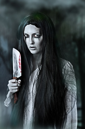 Portrait of a gory and scary zombie woman on black background holding knife photo