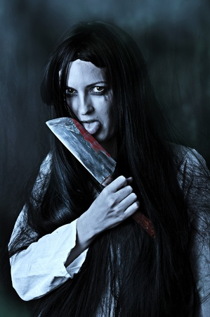 Portrait of a gory and scary zombie woman on black background licking bloody knife photo