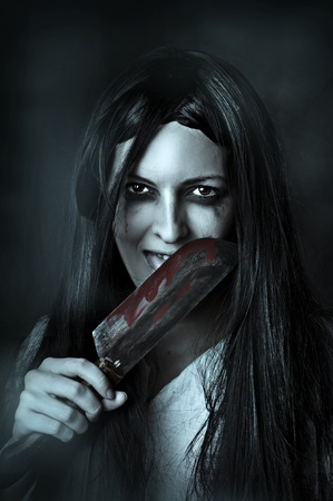 Portrait of a gory and scary zombie woman on black background licking bloody knife Stock Photo - 12390564