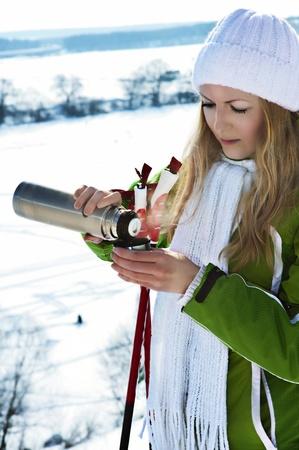 A beautiful caucasian girl drinking hot coffee at a ski resort  photo