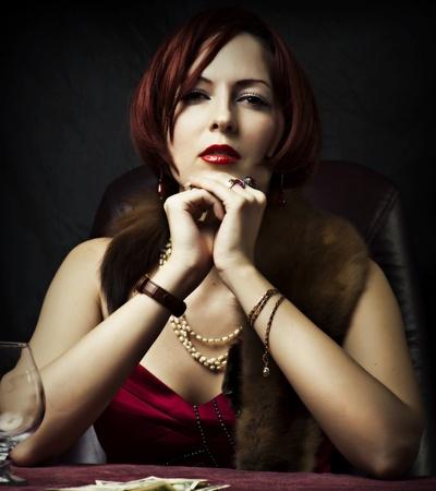 Glamour retrato de la cara de mujer sexy con maquillaje brillante por la noche para los anillos de oro del partido y las joyas con piedras preciosas que se sienta en la mesa Foto de archivo - 12390536
