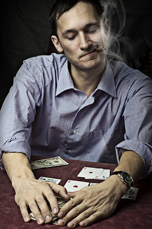 croupier: young man with cigar playing poker. Win Stock Photo