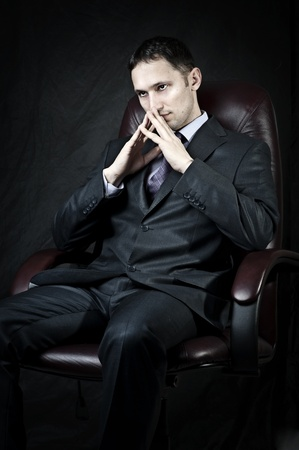 Young adult handsome businessman sitting on leather chair and thinking  photo